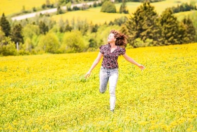 Girl running in field of yellow dandelion flowers