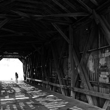 Two people exploring an abandoned covered bridge.