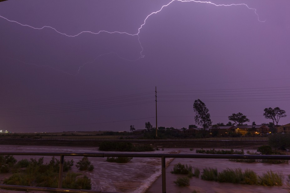 A wash in the desert is flooding while lightning lights up the water
