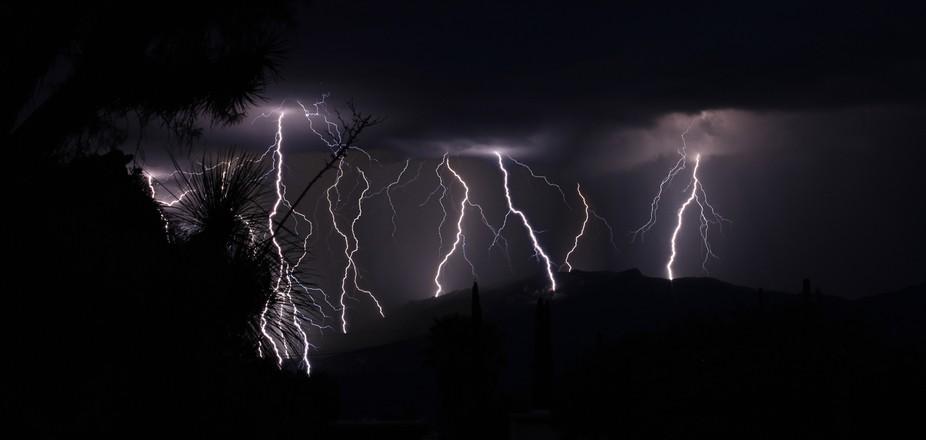 across a ridge of a mountain range the lightning walks its way.