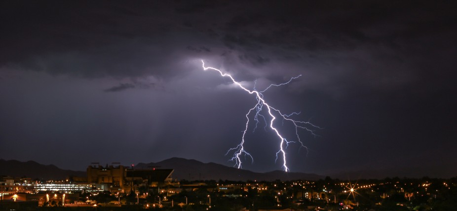 very powerful and long distant strikes light up a mountain ridge