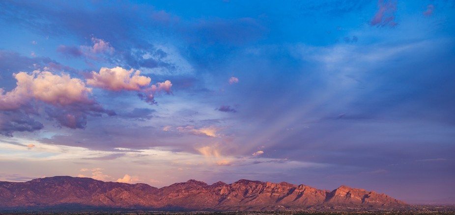 Rays and streaks with clouds as the mountains take on the sunset color