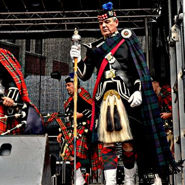 Pipes & Drums band on stage at a festival.