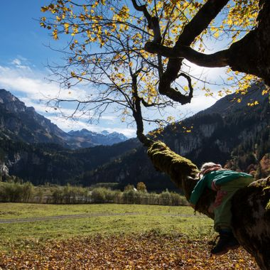 My daughter lying on at branch and enjoying the fall near Lake Tschingel in Kiental, Switzerland.