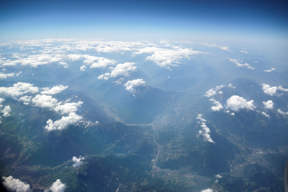 Taken at extreme height, the photograph shows the rocky terrain of the French alps with windy riv...