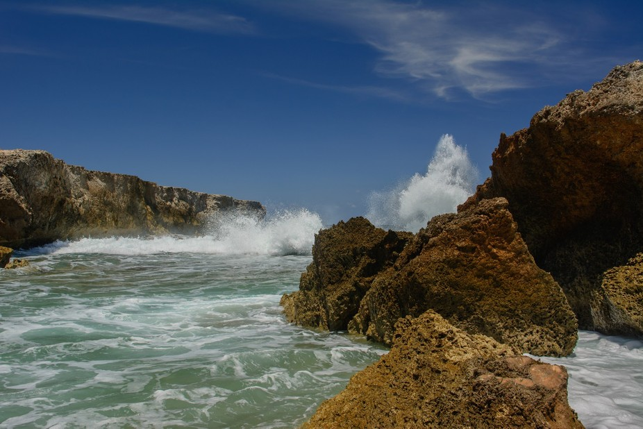 A splash of waves on rocks at a tiny beach on the north shore of Bonaire, one of the Dutch Antill...