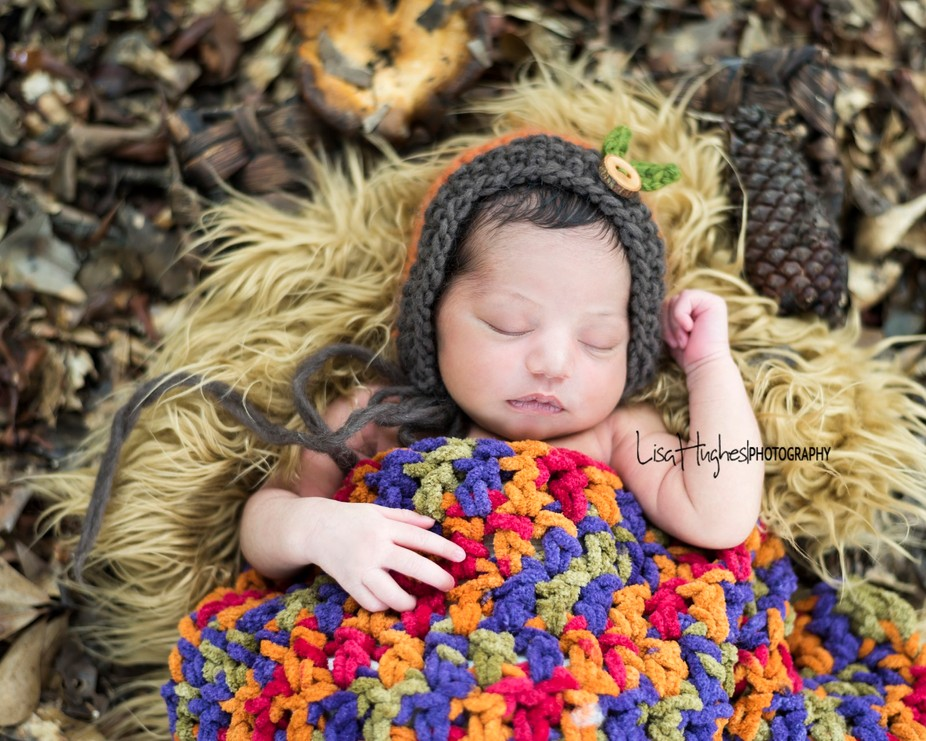 Fall baby sleeping in the woods in her orange bonnet