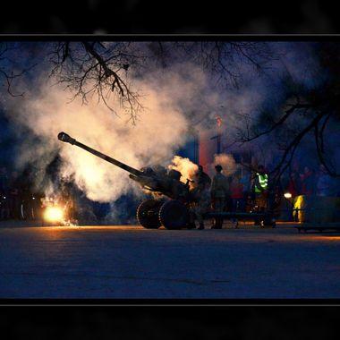 Artillery piece firing at night event.