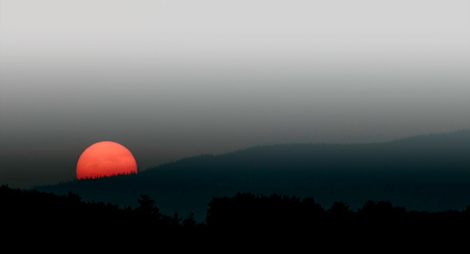 This was taken while  I was camping . The red sun is part of the effect of the smoky air we had d...