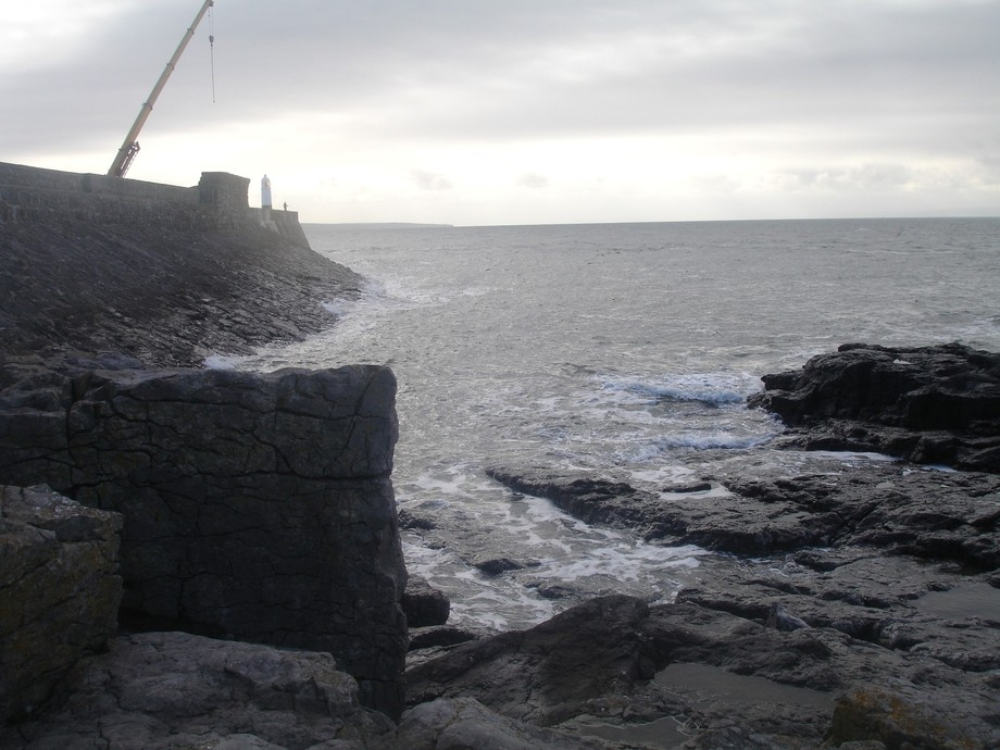 A lone fisherman trying his luck near the lighthouse. Porthcawl Wales UK.