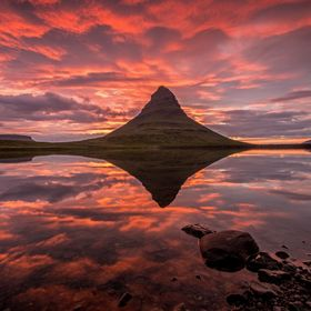 the famous Mount Kirkjufell on Iceland with a beautiful burning sky at midsummer