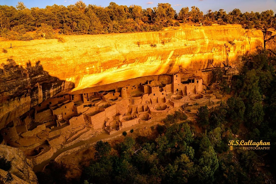 The last of the day's sunlight illuminates the upper face of the cliff above the Anasazi ruins.