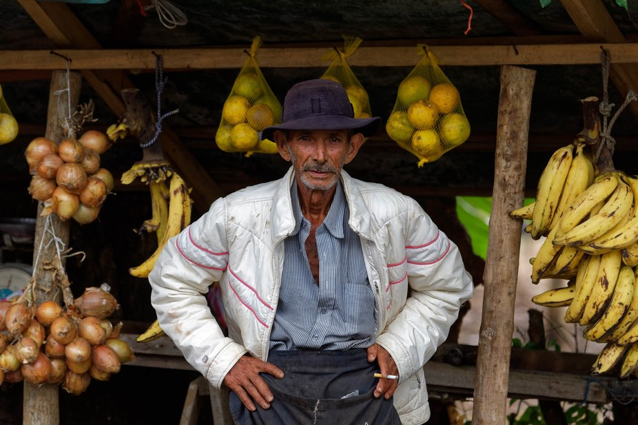 An old man is selling fresh fruits and vegetables at the street. Even if his shop looked very poo...