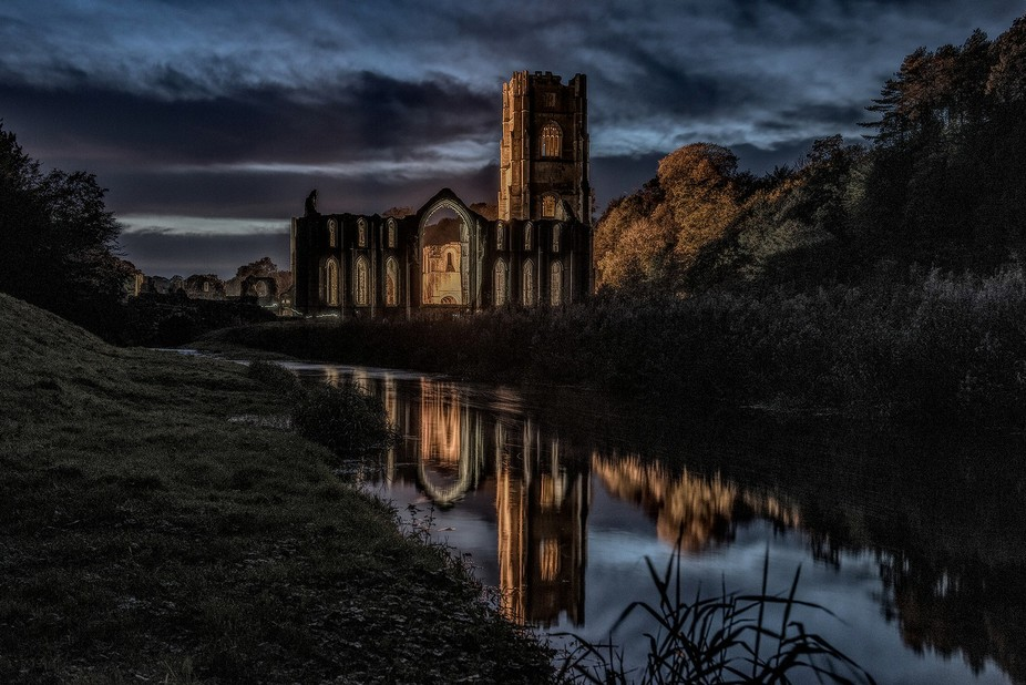 Fountains Abbey  reflected in the smooth flow of  the stream