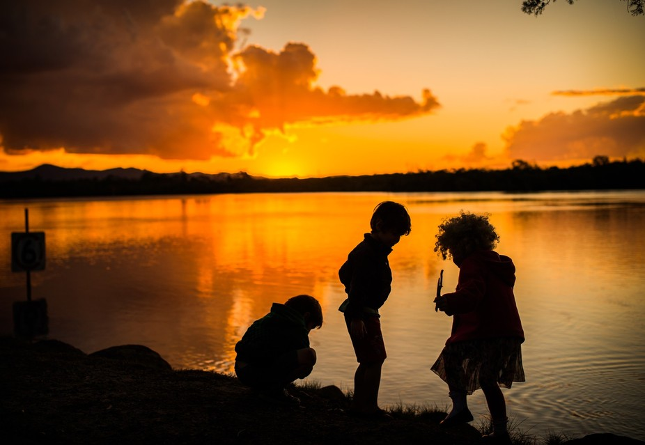 Enjoying a lovely late afternoon walk, I captured this image of my daughter and 2 nephews throwin...