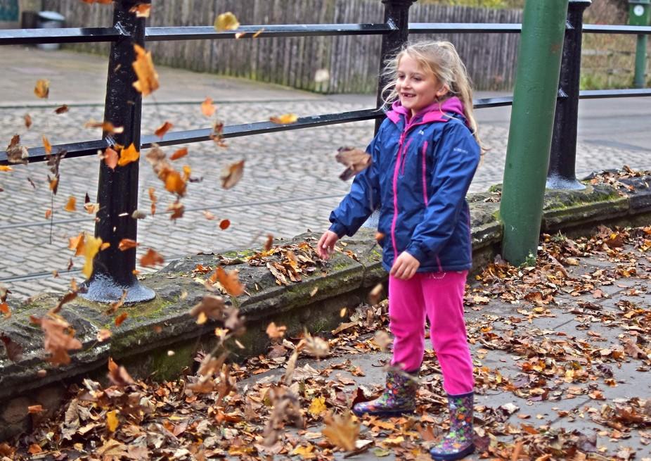 Little girl having fun throwing leaves