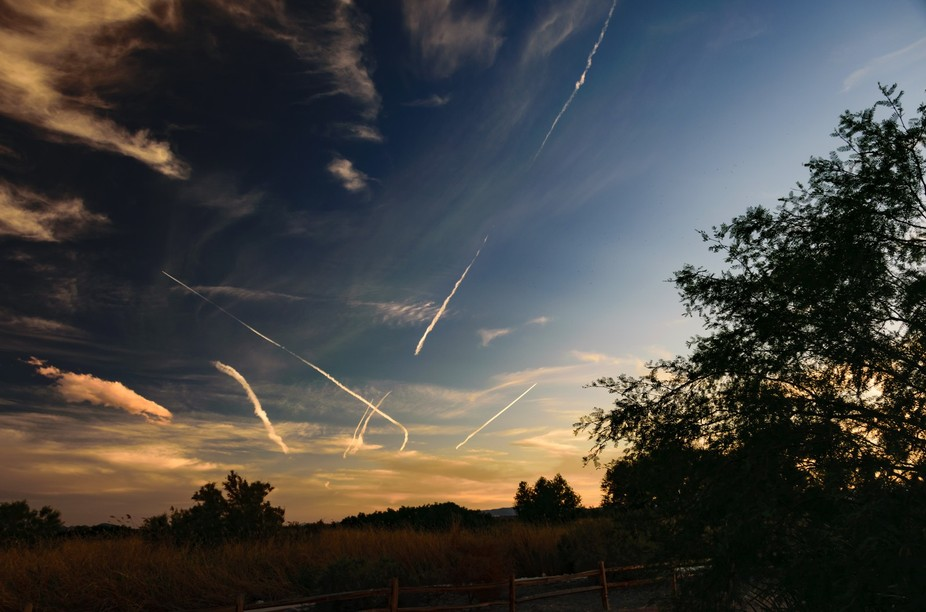 Planes fly overhead To destinations unknown Contrails paint the sky