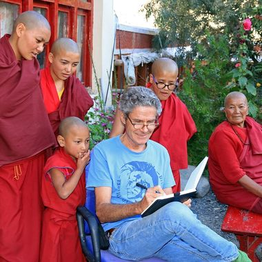 """The Swiss author """"Cosey"""" has written a series of illustrated books (in French: Bandes Dessinées) about the character Jonathan and his adventures in Ladakh. Here he is in the Lotsava School, Nurla, telling a story to a group of Buddhist novices."""
