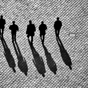 For a very short time this five men walk in a row just before someone passes their way. After a couple of seconds the group go their separat ways
