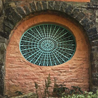 A wrought iron window decoration in a building wall at Portmeirion Village