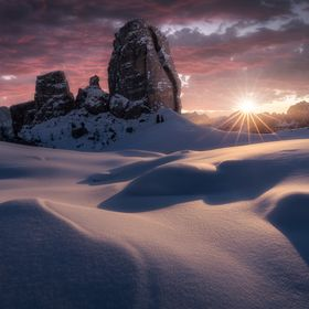 Sun is rising behind the amazing Cinque Torri in the Dolomites Mountainscape.