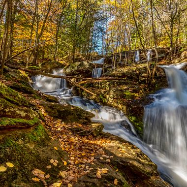 Autumn waterfall  with leaves on rocks and green moss