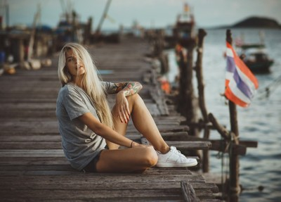 Hipster girl sitting on wooden pier in the rays of the setting sun. A vacation in Thailand. Hands with tattoos.