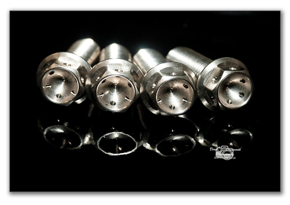 Racing bolts have the head drilled to take lock wire.  From a recent parts photography project