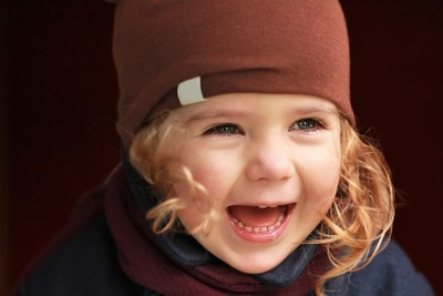 Close up portrait of a laughing one year old baby girl in brown hat coat and scarf against dark  background on a warm autumn day