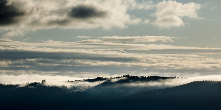 Clouds are creeping over the edge of the hills during an autumn morning in the Auvergne (France