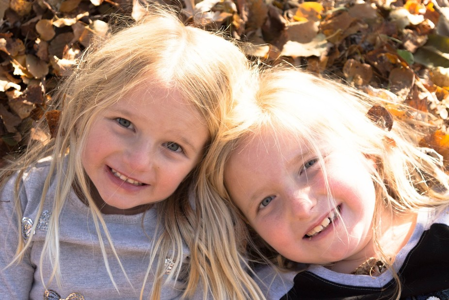 Sisters laying together in a pile of leaves, having some fun posing for they're daddy.
