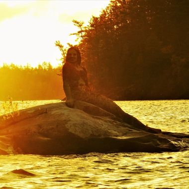 A bright foggy sunrise on the Rainy Lake Mermaid's back gave her and the water an interesting gold glow. Taken on Rainy Lake, Ontario, Canada Nikon Coolpix 6500