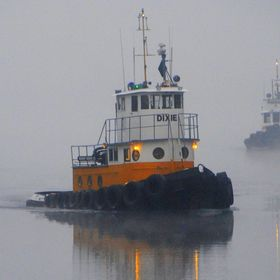 on the lake and coming home are two tugs in the fog