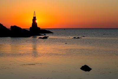 Sun peeks behind Ahtopol lighthouse in Black Sea in Bulgaria
