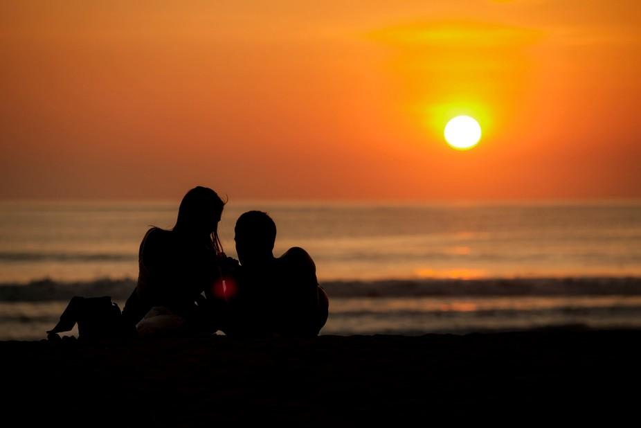 A honeymoon couple enjoying the sunset at Kuta Beach in Bali, Indonesia.