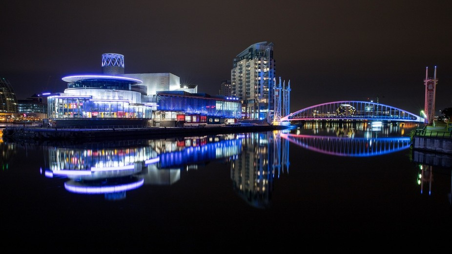 long exposure shot of buildings and bridge at Salford Quays, Manchester reflected in the water