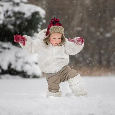 Baby walking through the winter snow.