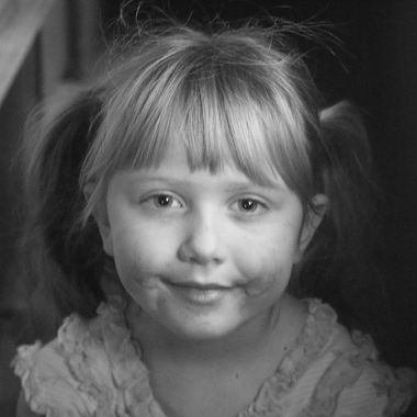 A smiling girl with a messy face just after a snack.
