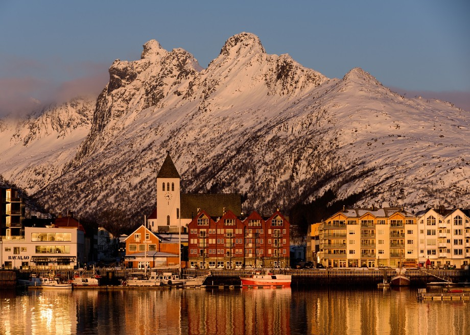 As the sun came over the horizon opposite Sovlaer in the Norwegian Lofoten islands in February it produced these beautiful reflections from the red apartments in front of the church with the snow cloud mountain towering above the town.