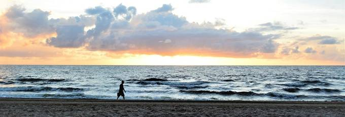 This man is strolling down the beach looking for a place to relax.
