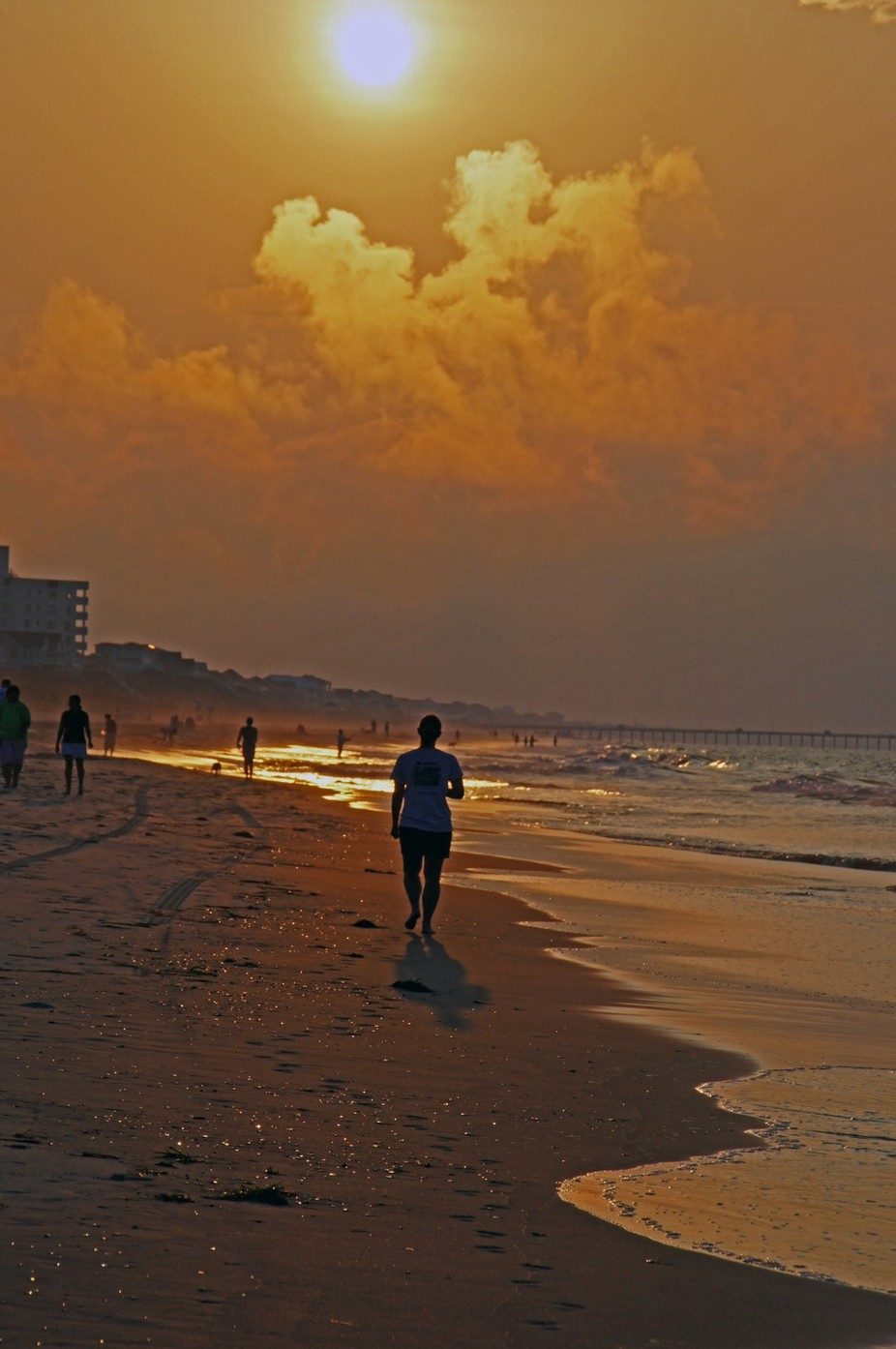 A copper sky in the early morning illuminates people walking on the beach.