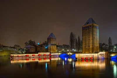 20171203-1809-DSC00102sNight view of highlighted medieval towers in Strasbourg with reflections in the water, France