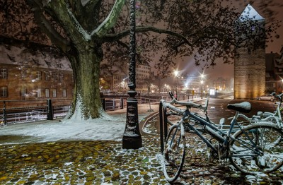 Snow-covered bicycles on the street, Strasbourg, night view, Christmas time, France