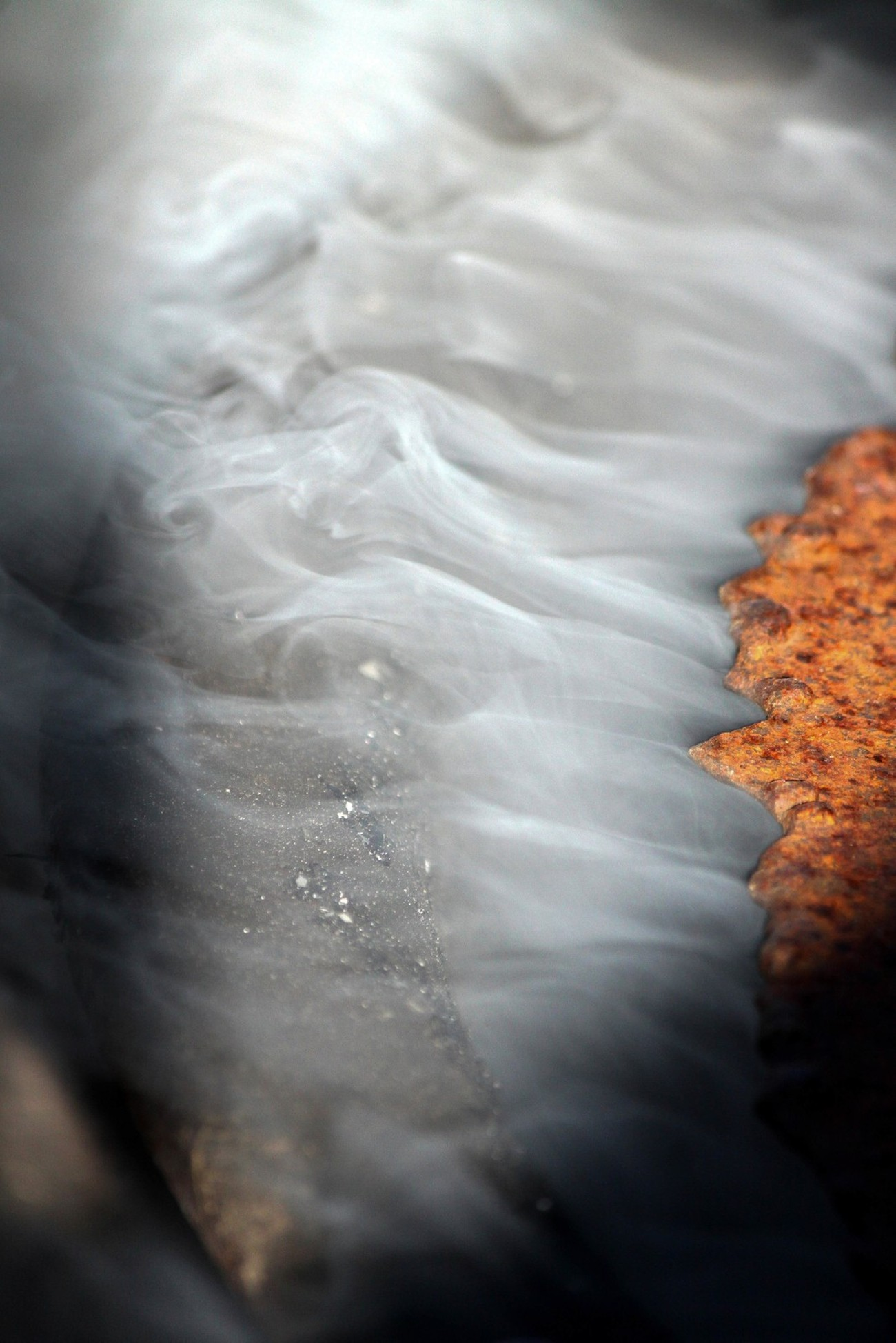 When I saw the smoke escaping from our bonfire pit, I knew I had to get a picture of it. The lid wasn't completely covering the pit so the smoke was billowing out in ripples.