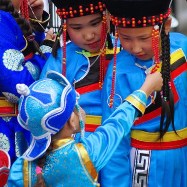 Each summer Mongolians celebrate Nadaam. As part of the Nadaam festivities in Ulaanbataar, people dress in traditional clothes from their particular regions of Mongolia. These children were waiting to participate in a cultural festival during Nadaam in Ulaanbataar.