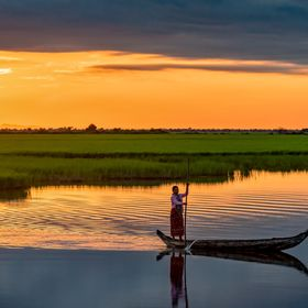 A woman returns home from harvesting rice in her field, as the first rays of sunlight begin to colour the dawn sky.  Her husband is catching fish...