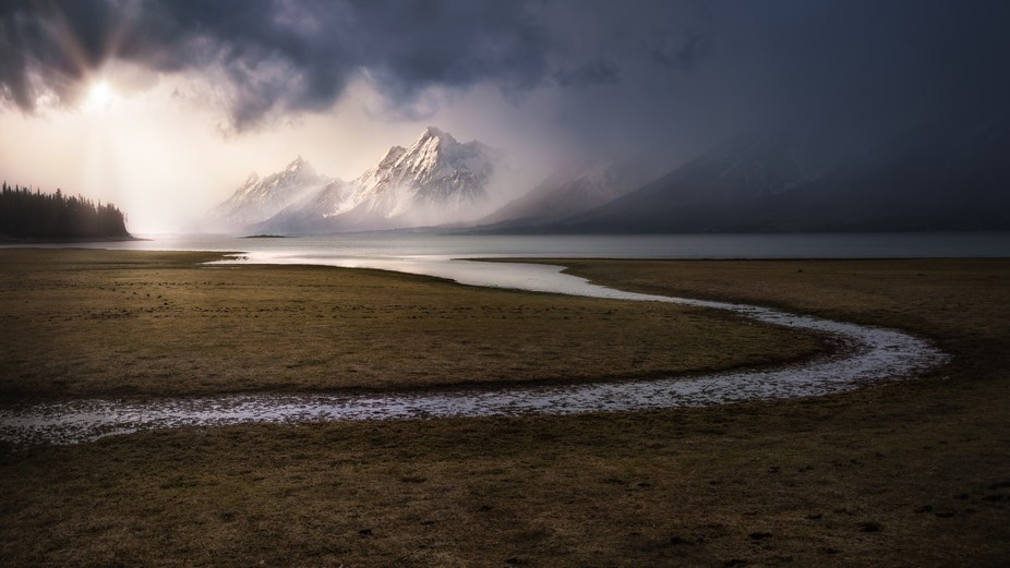 Fast moving storm begins to break apart exposing Grand Peak in a halo of morning light. A scene l...