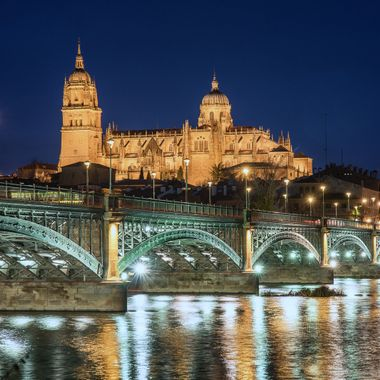 Blue hour shot of the Cathedral of Salamanca with the Enrique Estevan bridge in the foreground