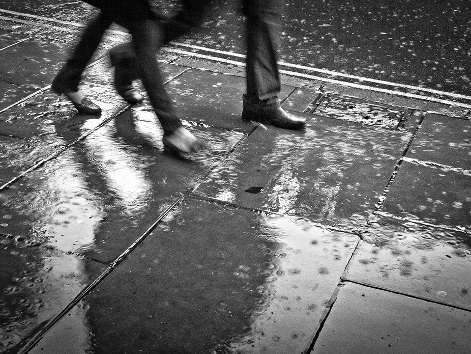 Rainy day in Nottingham with people scurrying along wet pavements.