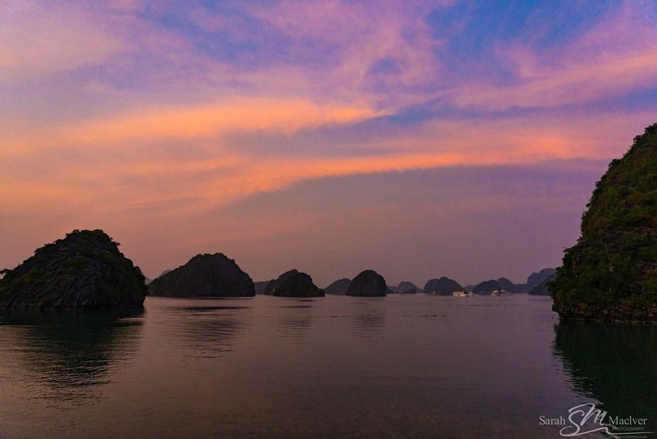 Sunset over the beautiful natural rock formations in Ha Long Bay, Vietnam